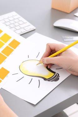 Photo. A graphic designer or web designer sketches a light bulb.