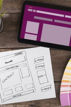 A visual designer drafts wireframes for a website and begins creating a prototype.