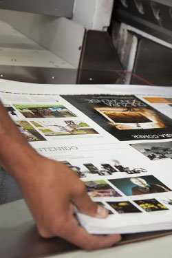 Photo. A production artist grabs page spreads out of a professional printer.