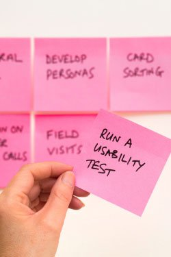 """Photo. A UX designer grabs a sticky note that says """"Run a usability test."""""""