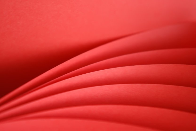 Photo. Designing for Digital vs. Print: folds of red paper.