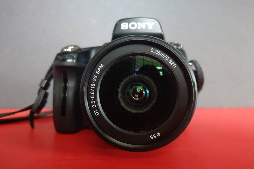Photo. Close-view of a camera on a red and black background.