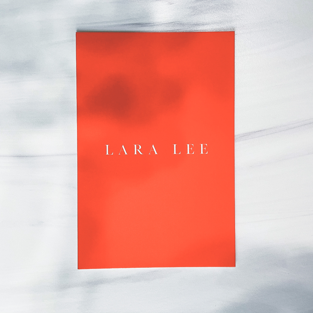 Photo of Lara Lee logo in red on a bright red card on a gray background with the shadows of leaves. This was one of the updates from my 2021 brand refresh.